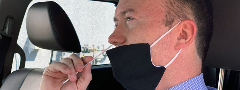 Man doing a self-administered nasal swab to test for COVID-19.