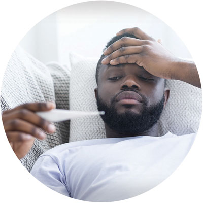 A man checks a thermometer to see if he has a fever, while holding his forehead.